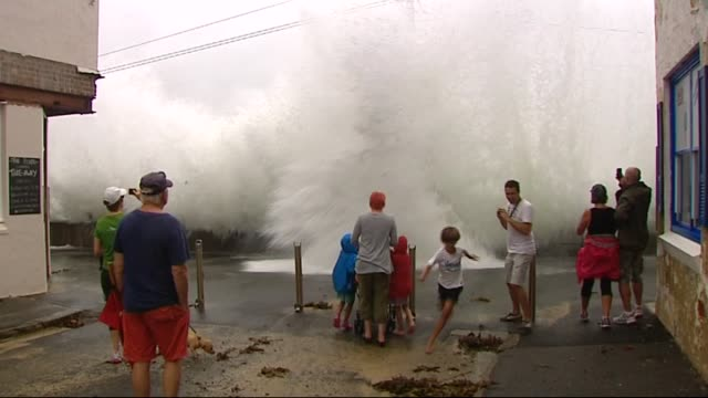 chris maher reports on havoc being caused by huge seas battering sydney's coastline: cabbage tree bay at manly - waves crashing over wall onto people... - drenched stock videos & royalty-free footage
