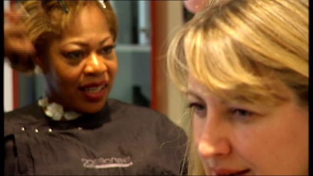 vídeos de stock, filmes e b-roll de chris rock documentary 'good hair'; reporter watching hairdresser in salon as chats with client michelle thompson - filme documentário
