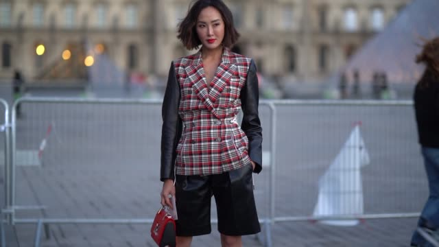stockvideo's en b-roll-footage met chriselle lim wears a red, white and black plaid jacket with black leather long sleeves, black leather shorts, a red louis vuitton bag, black heeled... - modeweek