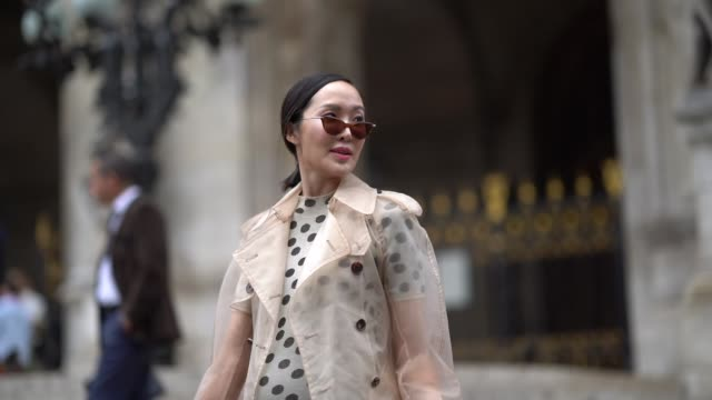 stockvideo's en b-roll-footage met chriselle lim wears a trench coat and a dress with polka dots outside schiaparelli during paris fashion week haute couture fall winter 2018/2019 on... - jurk