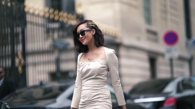 chriselle lim wears a white dress, a white bag, shoes, sunglasses, hair brooch, outside altuzarra, during paris fashion week womenswear fall/winter... - fashion week stock videos & royalty-free footage