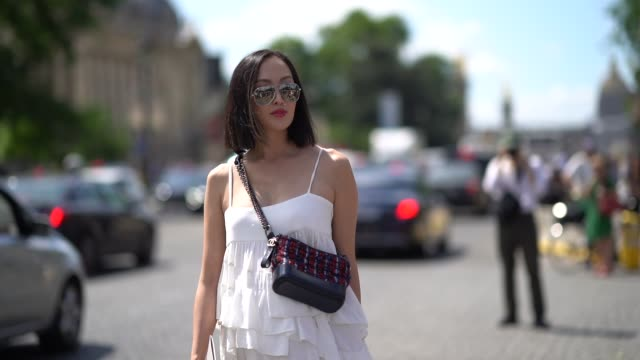 Chriselle Lim wears a white lace ruffled dress a Chanel bag red high leather boots outside Chanel during Paris Fashion Week Haute Couture Fall Winter...