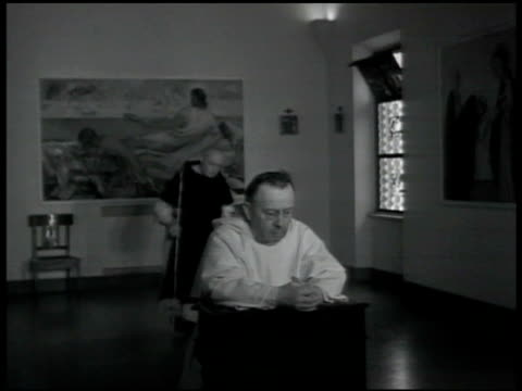 christian cross under archway chapel priest kneeling in prayer w/ another passing bg genuflecting candles being lighted below mural on wall of jesus... - priest stock videos and b-roll footage
