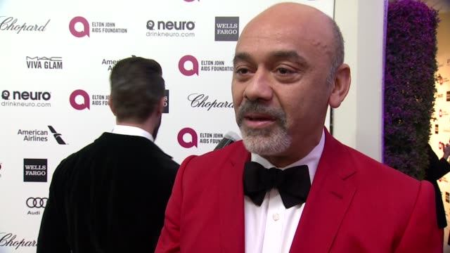 vídeos de stock, filmes e b-roll de interview christian louboutin on being at the event and on elton john at the 23rd annual elton john aids foundation academy awards viewing party... - festa do oscar