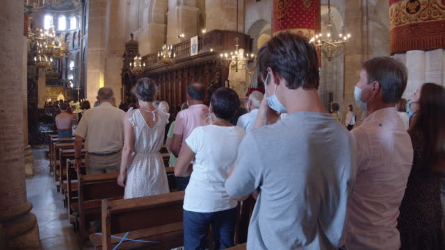 christian mass during coronavirus pandemic at toulouse france. people wearing masks inside cathedral - praying stock videos & royalty-free footage