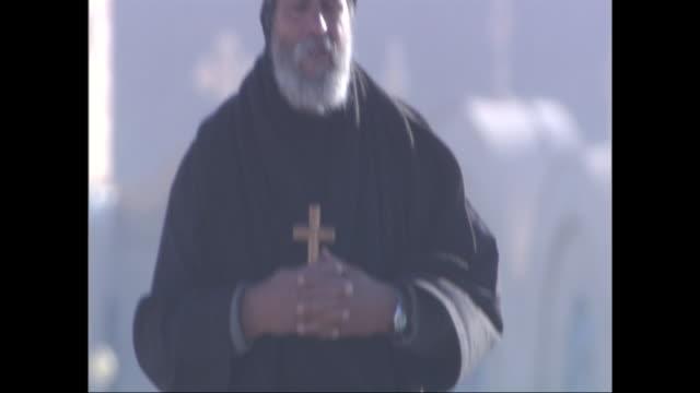 vidéos et rushes de a christian monk carries a crucifix as he walks along a road in the wind. - christianisme