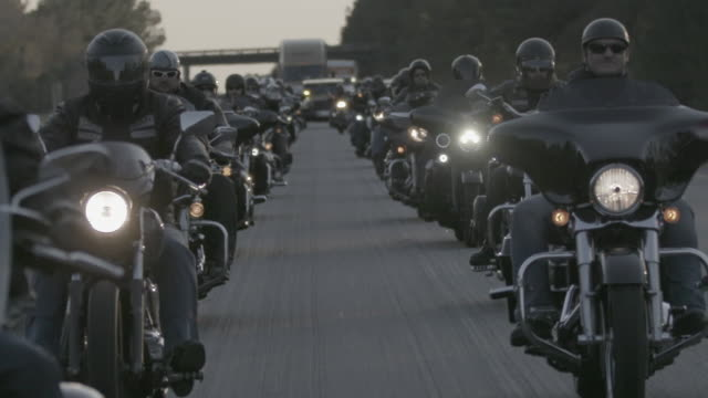 christian motorcycle club cruises down highway, slow motion - biker gang stock videos & royalty-free footage
