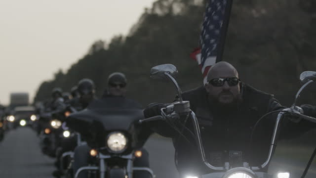 christian motorcycle club cruises down highway, slow motion - motorcycle biker stock videos & royalty-free footage