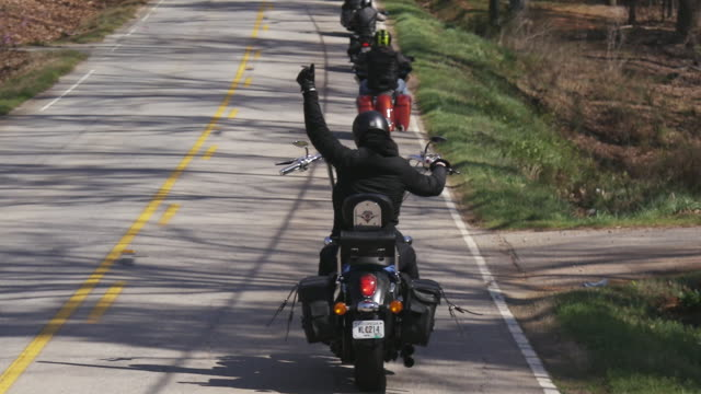 christian motorcycle club drives down road single file, slow motion - bande stock-videos und b-roll-filmmaterial