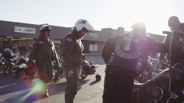 christian motorcycle club hanging out in parking lot - motorradfahrer stock-videos und b-roll-filmmaterial