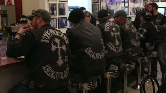 christian motorcycle club members eat at diner - motorradfahrer stock-videos und b-roll-filmmaterial