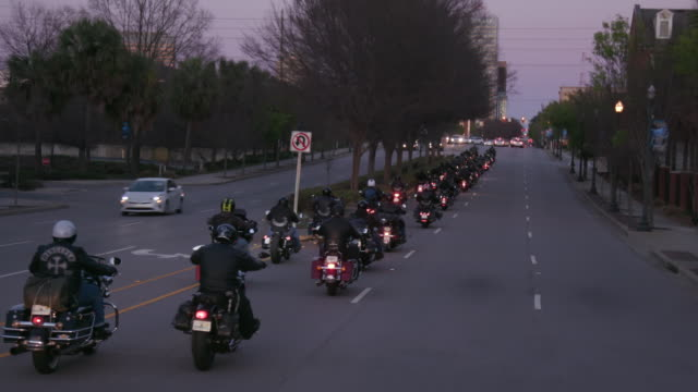 christian motorcycle club members ride down road - bande stock-videos und b-roll-filmmaterial