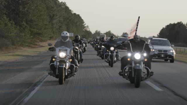 Christian motorcycle club rides on highway, medium shot