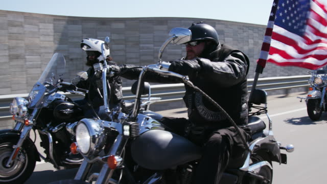 christian motorcycle gang drives on highway - bande stock-videos und b-roll-filmmaterial
