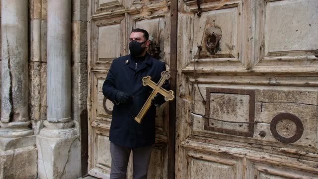 christian pilgrim wearing protective mask amid the covid-19 outbreak, holds a cross while making his way alone in the procession of the way of the... - ヴィアドロローサ点の映像素材/bロール