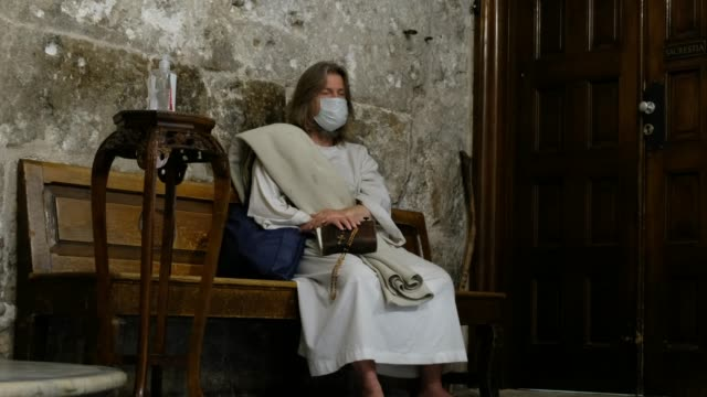 christian worshipper dressed as jesus christ wears a face mask inside the church of the holy sepulchre, located in the christian quarter of the old... - worshipper stock videos & royalty-free footage