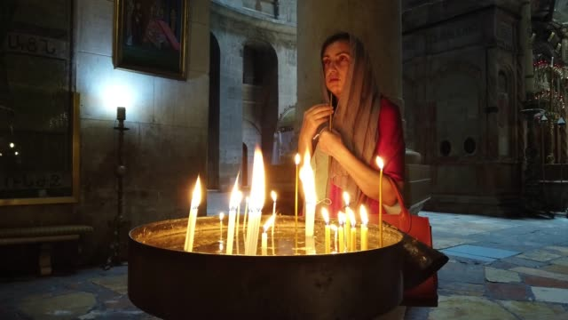 christian worshipper lights candles as she prays inside the church of the holy sepulchre, located in the christian quarter of the old city of... - worshipper stock videos & royalty-free footage