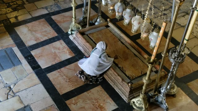 christian worshipper prays by the stone of the unction in the church of the holy sepulchre, located in the christian quarter of the old city of... - worshipper stock videos & royalty-free footage