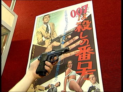 Christie's Auction Film memorabilia Close shot of James Bond handgun held in hand Japanese James Bond film poster in background