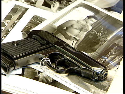 vídeos de stock, filmes e b-roll de christie's auction film memorabilia close shots of james bond handgun laid on james bond film stills - james bond trabalho conhecido