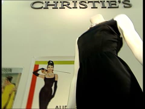 Christie's Auction Film memorabilia Vars black dress worn by Audrey Hepburn in 'Breakfast at Tiffany's' displayed on mannequin film posters in...