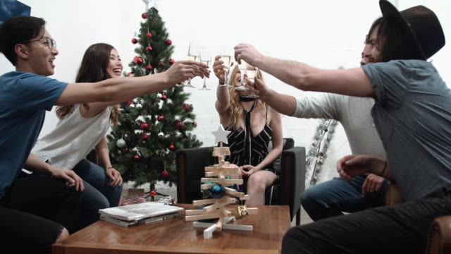 christmas: a group of friends toasting with champagne celebrating christmas - loft apartment stock videos & royalty-free footage