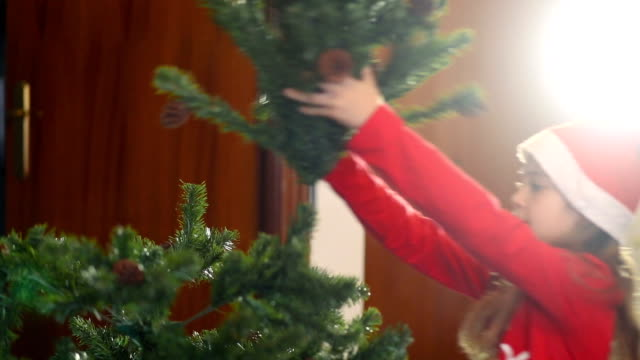 Christmas. Adorable little girl putting on a Christmas tree bigger than her.