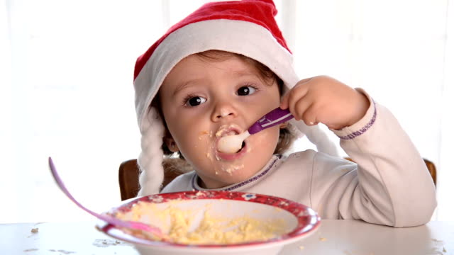 christmas baby girl eating and smiling - santa hat stock videos & royalty-free footage