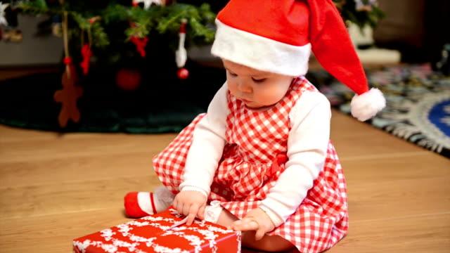 christmas baby girl opening present - 6 11 månader bildbanksvideor och videomaterial från bakom kulisserna
