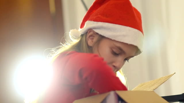 Christmas. Beautiful little girl with Santa Clauss hat looking inside a cardboard box.