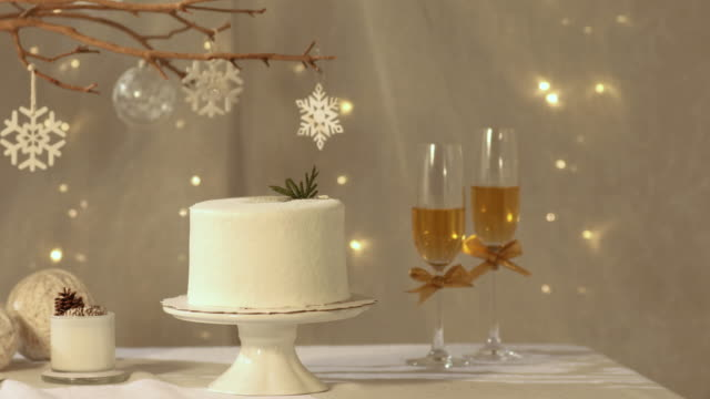 stockvideo's en b-roll-footage met christmas cake and a glass of champagne on the table - dennenappel