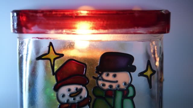 christmas candle burning inside a seasonal container - christmas decore candle stock videos & royalty-free footage