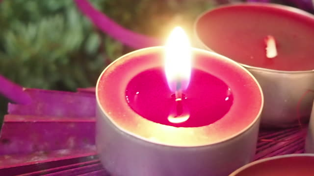 christmas candles. moving around lit candle. wax candle. advent. germany, europe. - purple stock-videos und b-roll-filmmaterial