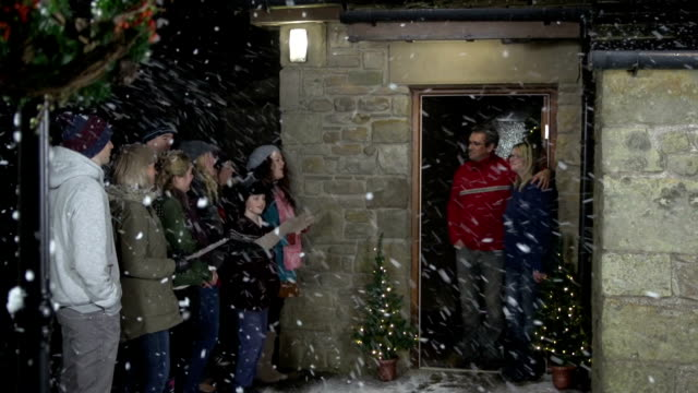 christmas carol singers, singing at a house in the snow - carol singer stock videos & royalty-free footage