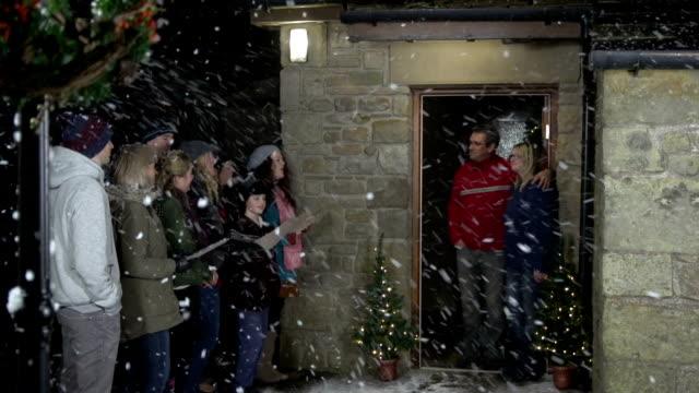 christmas carol sängern, singen in einem haus im schnee - chorsänger stock-videos und b-roll-filmmaterial