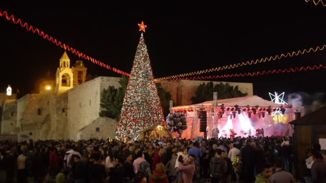 christmas celebration at manger square, church of the nativity in bethlehem, westbank, palestine. medium wide shot. - church of the nativity stock videos and b-roll footage
