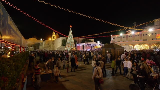 christmas celebration at manger square, church of the nativity in bethlehem, westbank, palestine. wide shot. - church of the nativity stock videos and b-roll footage