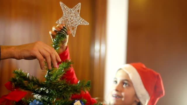 Christmas. Cheerful family helping each others to put a star on the Christmas tree.