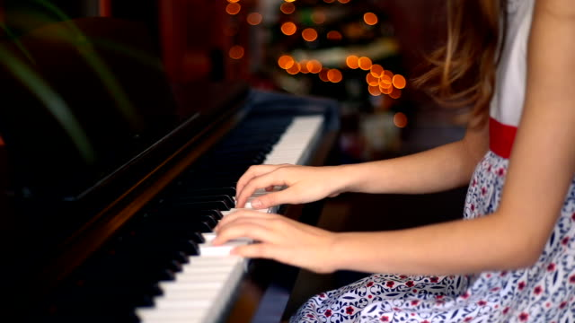 Christmas. Close up of the hands of a girl playing the piano. Christmas lights in background.