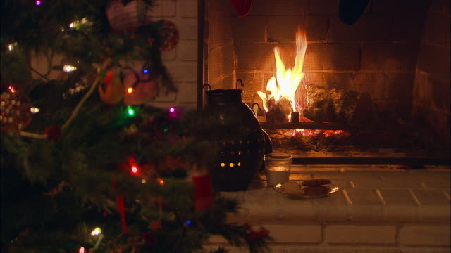cu, selective focus, christmas cookies and glass of milk for santa next to fireplace, christmas tree in foreground - 暖炉点の映像素材/bロール