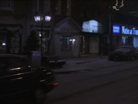 christmas decorations adorn shops on a small town street. - kryssa bildbanksvideor och videomaterial från bakom kulisserna
