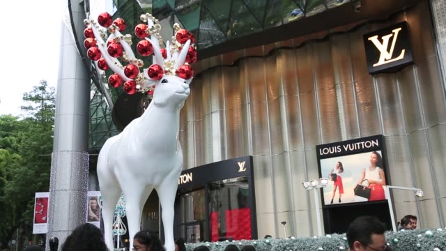 Christmas decorations are displayed near Orchard Road in Singapore on Sunday Dec 16 Pedestrians walk past a Christmas tree and festive decorations...