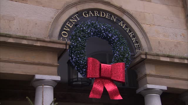 christmas decorations at covent garden market; england: london: covent garden: ext wide shot christmas trees on display in front of market and sign... - blinking stock videos & royalty-free footage