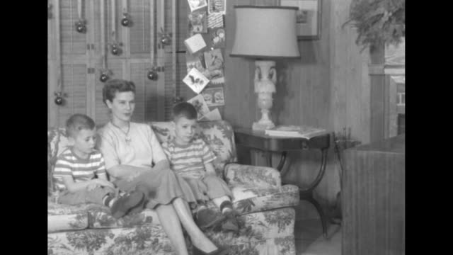 vs christmas decorations behind them patricia wife of captain harry f hedlund and two sons larry tom sit on sofa for reaction shots / she gets up to... - 1950 stock videos and b-roll footage
