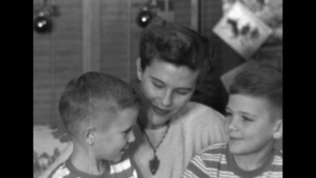 christmas decorations behind them, wife of captain harry f hedlund, patricia and two sons larry & tom, snuggle on sofa and talk about hedlund: she... - letter b stock videos & royalty-free footage