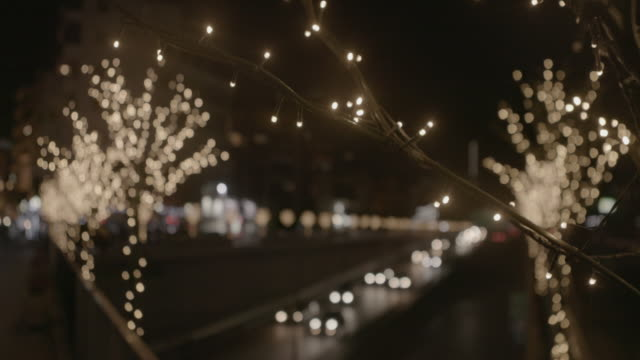 christmas decorations, beirut. night rack-focus between flowing traffic and trees decorated with fairy-lights on the furn el-chebbak highway. - glittering stock videos & royalty-free footage