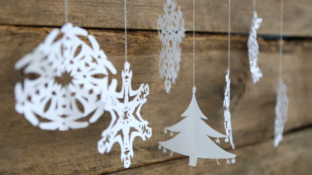 christmas decorations snowflake ,tree paper hanging over wooden background - christmas paper stock videos and b-roll footage