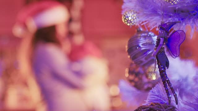 weihnachtsfee. junge mutter mit ihrem neugeborenen baby feiert die weihnachtsferien während covid-19 pandemie zu hause. tanzen und telefonieren mit der familie, während sie zu hause in quarantäne bleiben. die neue normalität. - weihnachtsmütze stock-videos und b-roll-filmmaterial