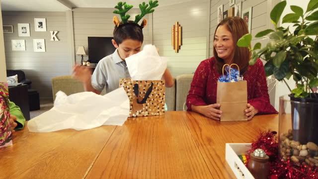stockvideo's en b-roll-footage met kerstcadeau uitwisseling met opgewonden koreaanse etnische familie met gemengde ras kinderen 4k video-serie met bijpassende foto's - cadeau