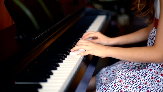 christmas. girl playing the piano with the christmas tree behind. - piano stock videos and b-roll footage